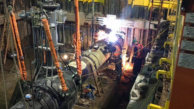 Workers and machinery working on gas pipes